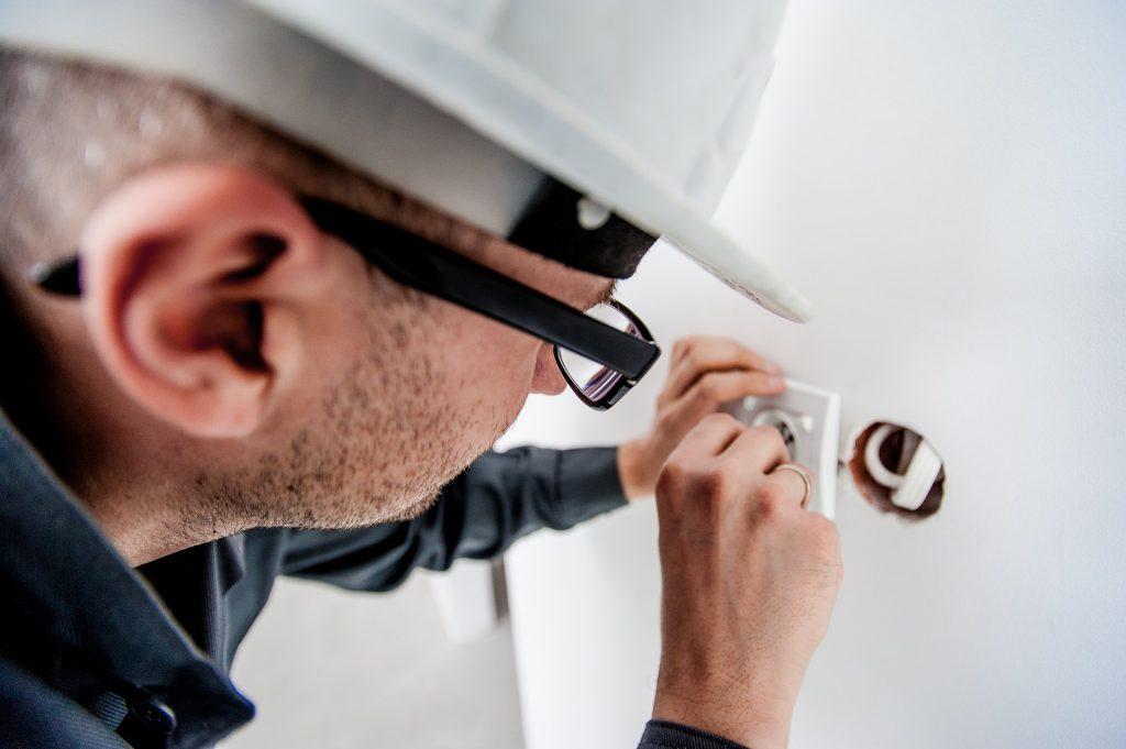 un electricien avec un casque qui travaille sur une prise de courant