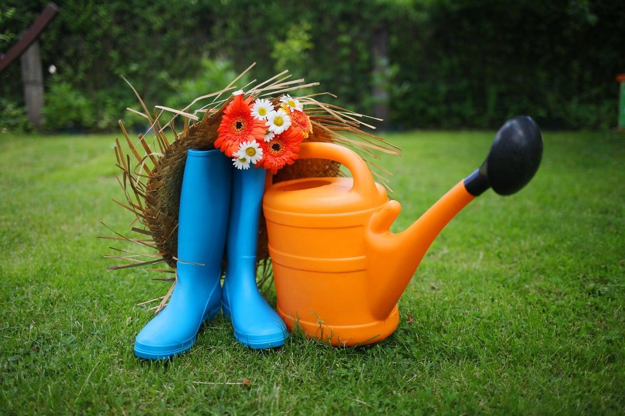 bottes en caoutchouc bleues, arrosoir orange, bouquet de fleurs et chapeau de paille