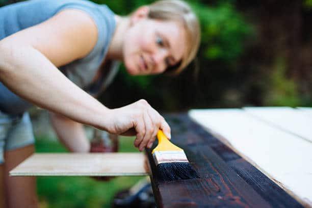 Jeune femme qui applique une couche de lasure sur du bois pour le protéger