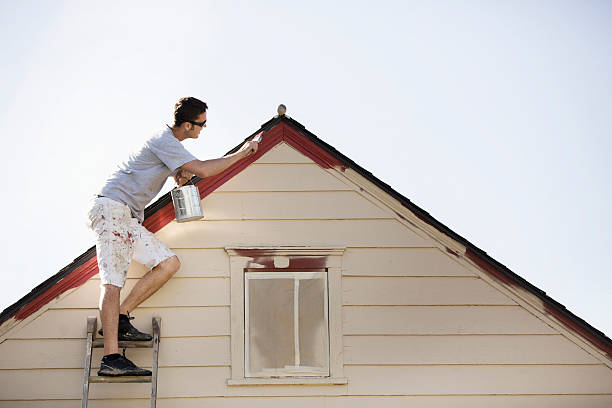 Homme qui repeint sa maison lors de sa rénovation extérieure